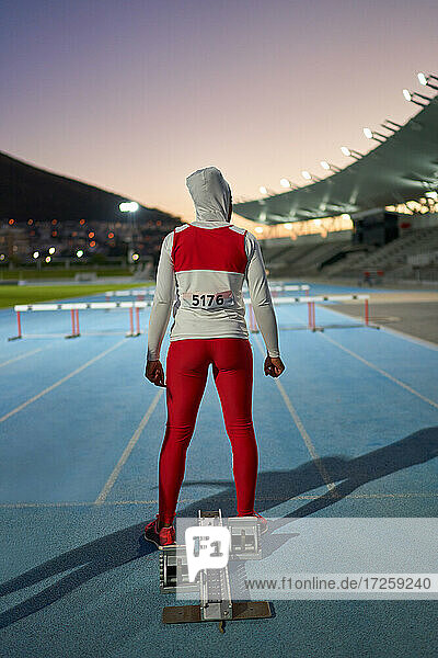 Female track and field athlete in hijab at starting block on track
