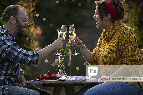 Happy couple enjoying champagne and red currants at patio table