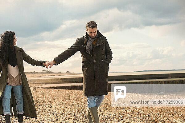 Paar in Wintermäntel halten Hände zu Fuß auf sonnigen Strand