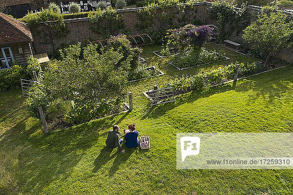 Couple taking a break from gardening in sunny idyllic lush garden