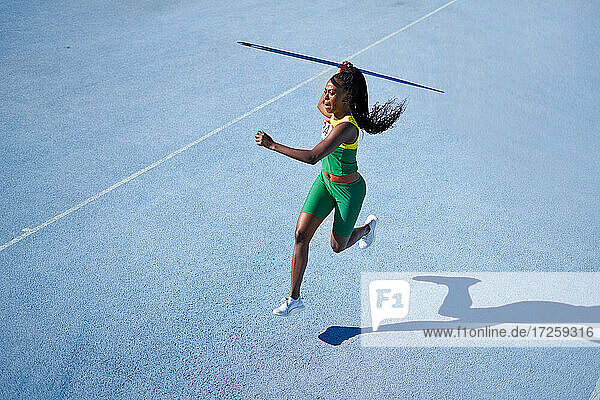 Female track and field athlete throwing javelin on sunny blue track
