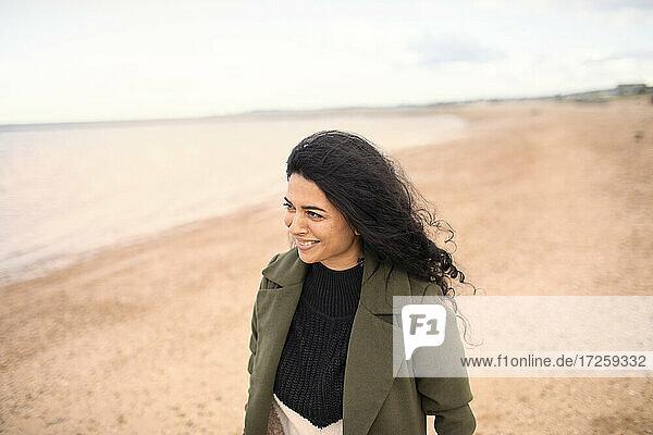 Glückliche Frau im Winter Mantel auf Winter Ozean Strand