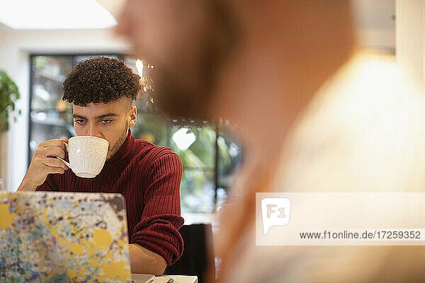 Junger Mann trinkt Kaffee und arbeitet von zu Hause aus am Laptop