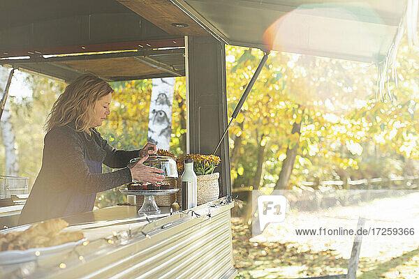Weiblicher Foodtruck-Besitzer arrangiert Gebäck im sonnigen Herbstpark