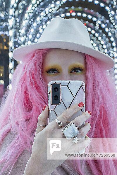 Porträt kühlen stilvolle Frau mit rosa Haaren und Fedora unter Selfie