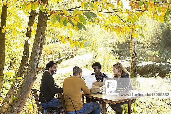 Kreatives Business-Team trifft sich am Tisch im sonnigen  idyllischen Herbstpark