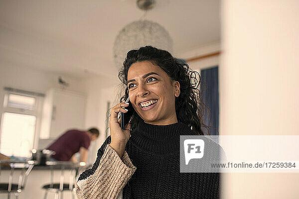 Glückliche Frau spricht auf Smartphone zu Hause