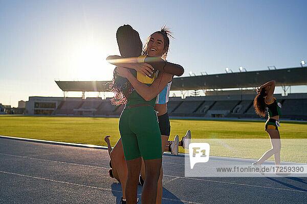 Glückliche weibliche Leichtathleten  die sich auf einer sonnigen Strecke umarmen