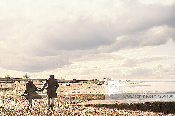 Couple holding hands walking on sunny tranquil winter beach