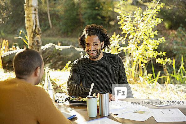 Geschäftsleute essen zu Mittag und besprechen Papierkram am Parktisch
