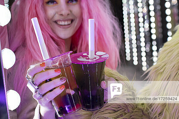 Happy stylish woman with pink hair holding cocktails in disposable cup