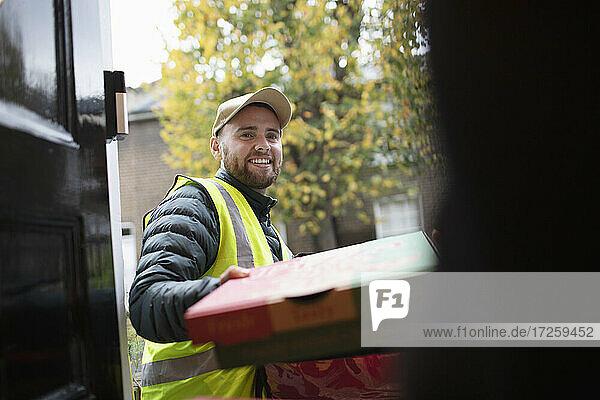 Freundlicher Pizzabote liefert Pizza an der Haustür