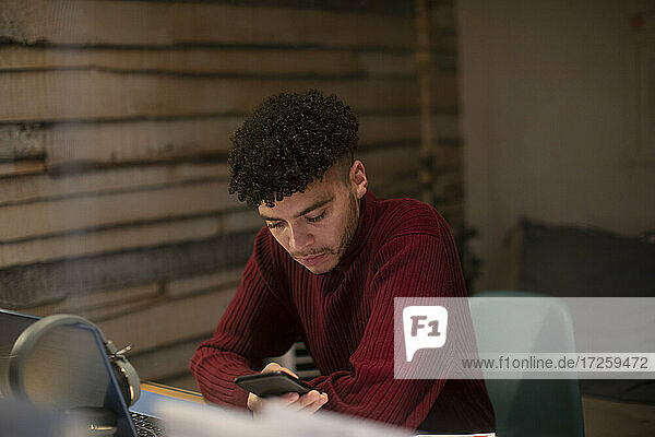 Konzentrierter junger Mann mit Smartphone bei der Arbeit im Home Office