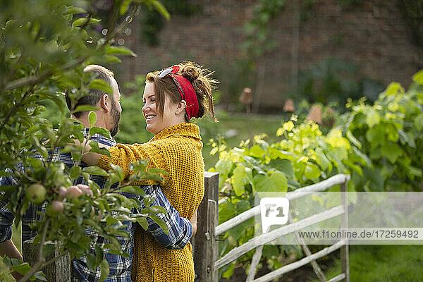 Glückliches Paar umarmen und reden im Garten
