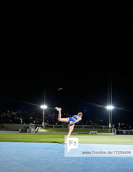 Weibliche Leichtathletin wirft Diskus im Stadion bei Nacht