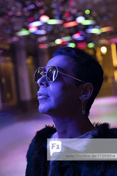 Porträt stilvoller junger Mann mit Sonnenbrille schaut auf Neonlichter