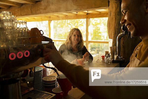 Barista preparing coffee for customer at espresso machine in cafe