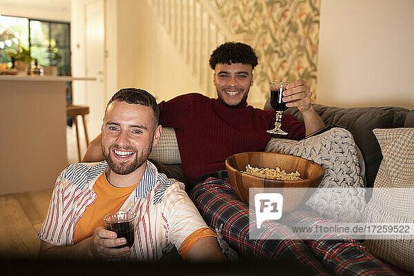 Glückliche Homosexuell männliches Paar mit Wein und Popcorn beobachten Film