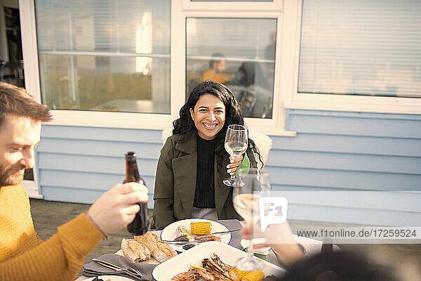 Glückliche Frau genießt Wein und Meeresfrüchte mit Freunden auf der Terrasse Tisch