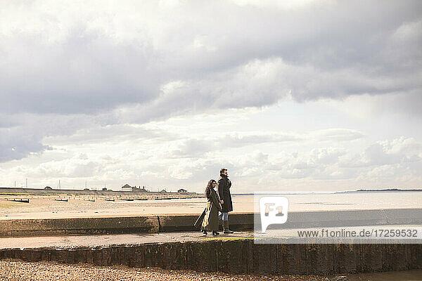 Paar in Wintermäntel zu Fuß auf sonnigen Winter Ozean Strand Steg