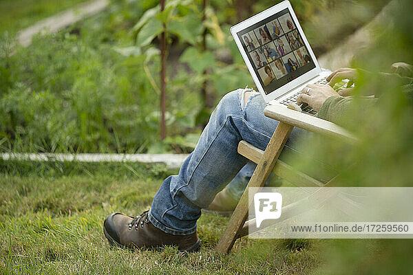 Mann arbeitet am Laptop im Gemüsegarten