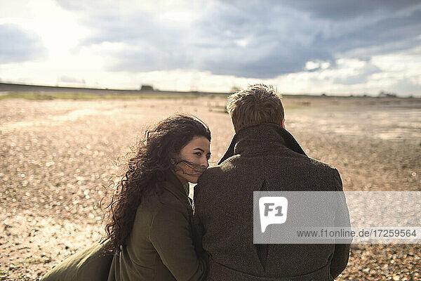 Paar in Mänteln auf sonnigen windigen Winterstrand