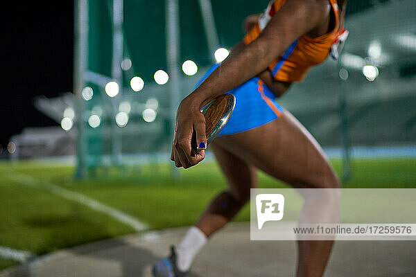 Female track and field athlete throwing discus