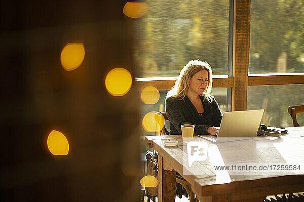 Geschäftsfrau arbeitet am Laptop in einem sonnigen Cafe