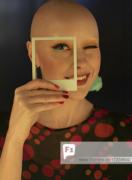Porträt modische Frau mit rasiertem Kopf und Polaroid Ausschnitt