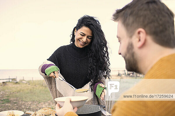 Happy woman serving chowder to boyfriend on beach patio