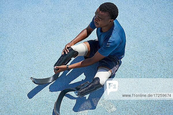 Männlicher amputierter Sprinter bei der Vorbereitung auf der blauen Sportbahn
