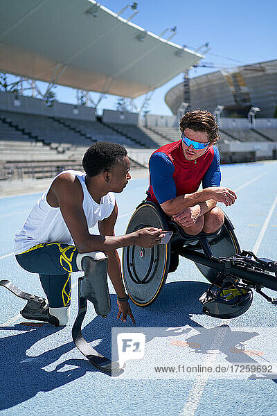 Male amputee and wheelchair athletes talking on sunny sports track