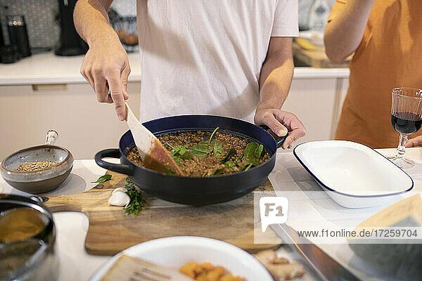 Junger Mann kocht Abendessen in der Küche