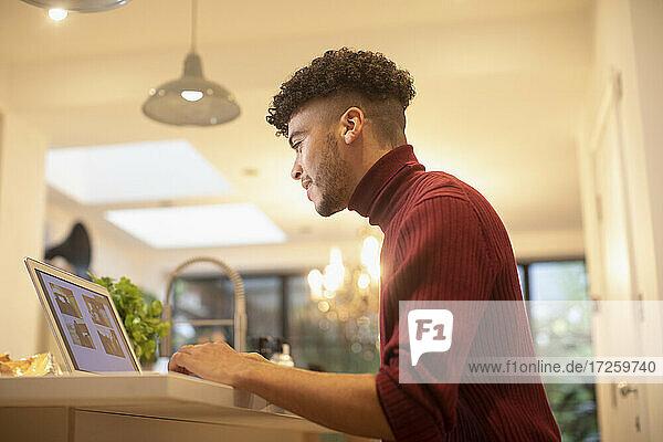 Junger Mann arbeitet von zu Hause aus am Laptop in der Küche