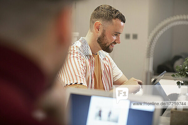 Glücklicher junger Mann  der von zu Hause aus an einem digitalen Tablet arbeitet