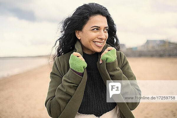 Glückliche schöne Frau im Wintermantel am Strand