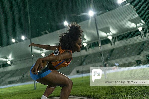 Weiblicher Leichtathlet beim Diskuswurf im Stadion