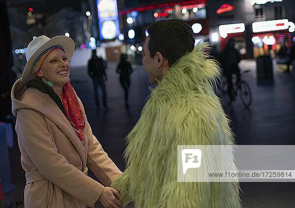 Glückliche stilvolle Paar hält die Hände auf Stadt Straße in der Nacht