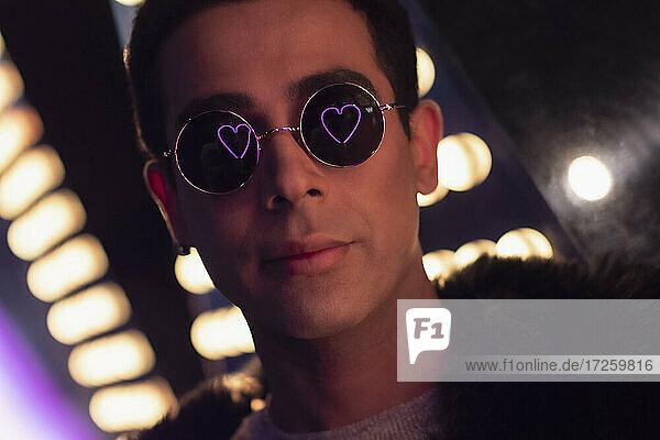 Porträt kühlen jungen Mann mit Neon Herz Reflexion in Sonnenbrille