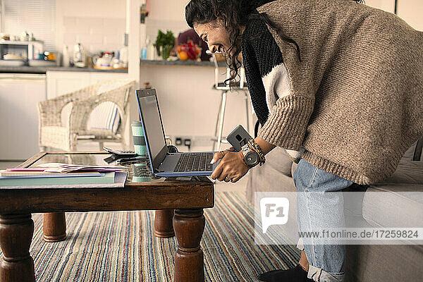 Glückliche Frau arbeitet von zu Hause am Laptop im Wohnzimmer