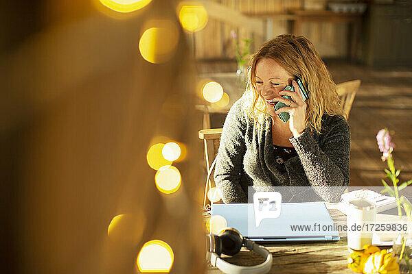 Glückliche Geschäftsfrau spricht auf Smartphone in sonnigen Café
