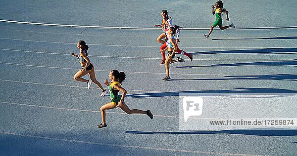 Leichtathletinnen im Wettkampf auf blauer Bahn