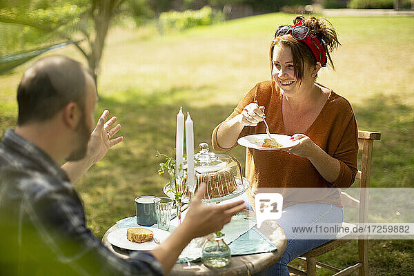 Happy couple enjoying cake and tea at sunny garden table