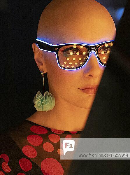 Close up Porträt stilvolle Frau mit rasiertem Kopf in Neon-Brille