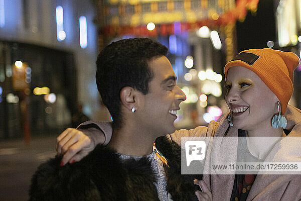 Happy stylish couple on city street at night