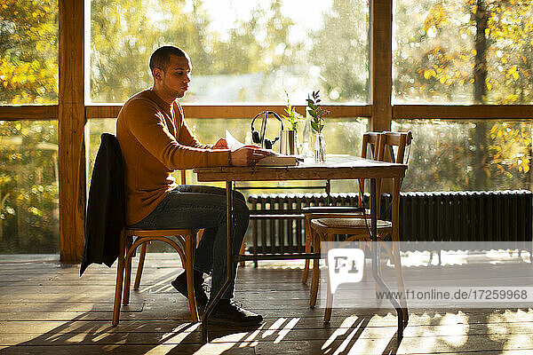 Businessman with paperwork working in sunny autumn cafe