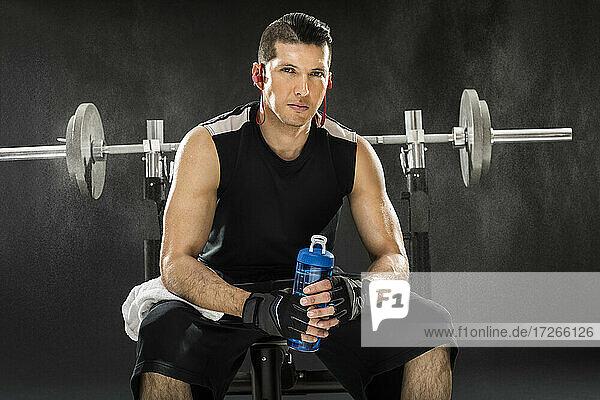 Muskulöser Mann Training mit Langhantel und hält Wasserflasche