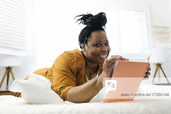 Lächelnde Frau liest Buch im Bett