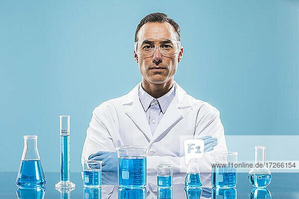 Porträt eines Wissenschaftlers mit Bechern mit blauer Flüssigkeit im Vordergrund