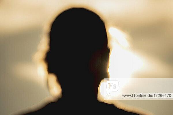 Unscharfe Silhouette eines Frauenkopfes bei Sonnenuntergang